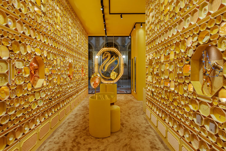 Loja com paredes cobertas por caixas da Swarovski em forma de octógono douradas. Vitrine ao fundo com novo logo de cisne dourado em luz