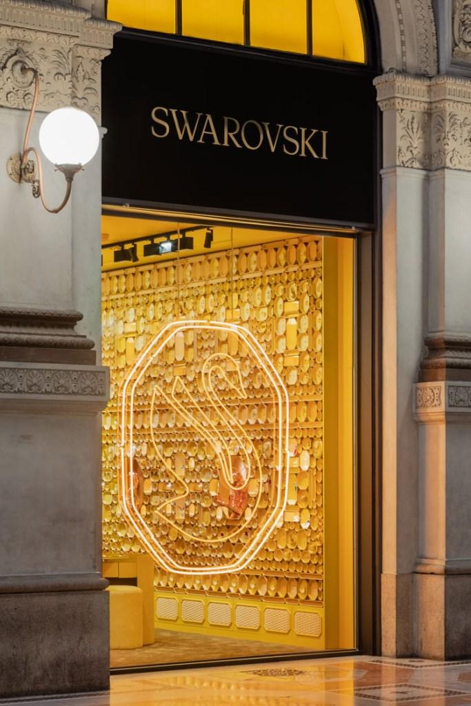 Foto vertical da fachada da loja com logo de cisne iluminado no vidro.