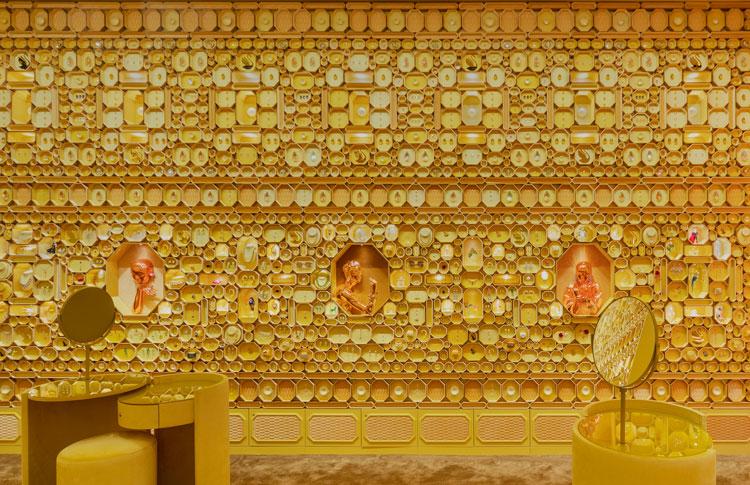 Parede coberta com caixas de diferentes tamanhos douradas. Mesinhas com pufes também amarelos.