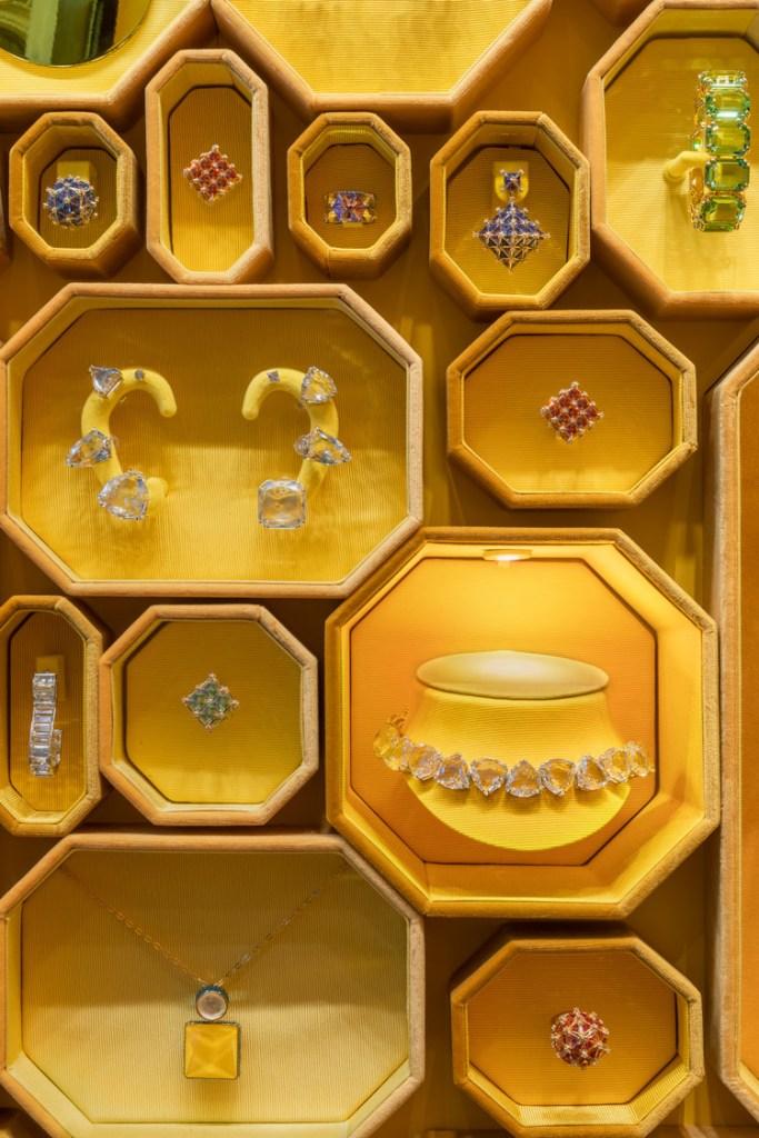 Detalhe das joias, brincos, colares e aneis nas caixas octogonais amarelas na parede