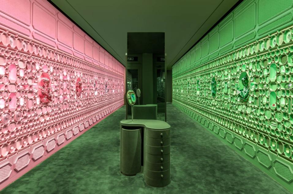 Loja com paredes cobertas por caixinhas octogonais da Swarovski. Parede da esquerda rosa, parede da direita verde.