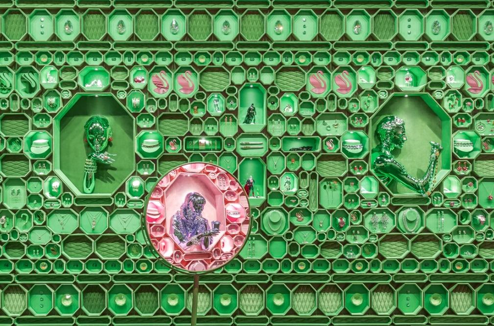 Parede coberta com caixas octogonais verdes. Espelho no canto inferior esquerdo reflete a parede rosa do lado oposto.