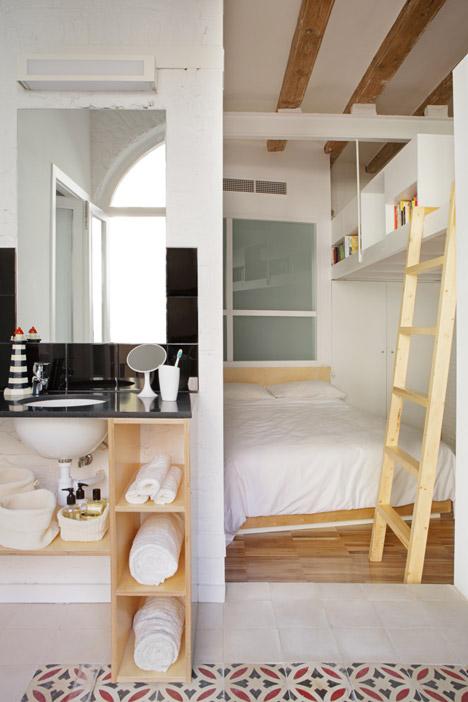 Quarto com cama e escada em madeira. Ao lado, banheiro com pia com bancada preta.