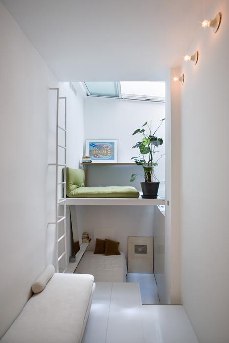 Quarto em dois níveis estreitos. Almofada verde, planta e quadro no andar de cima. Escada branca. No andar de baixo, cama.