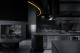 Ambiente monocromático: restaurante foca no preto e em cozinha em formato de palco