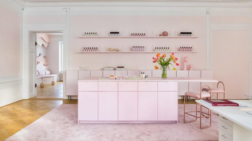 Sala do salão. Tapete e balcão rosa claro. Duas prateleiras com produtos na parede. Duas banquetas baixas no balcão.