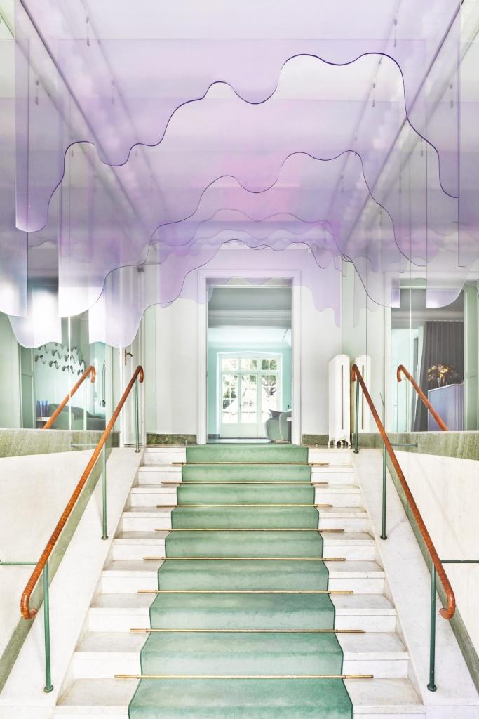 Escada branca com tapete verde. Espelhos nas laterais. Placas de acrílico roxas transparente no teto cortadas como se estivessem escorrendo e pingando