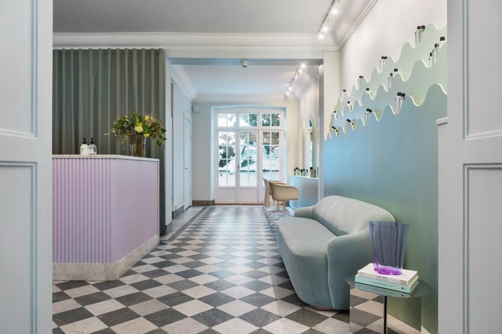 Lounge de entrada do salão. Piso quadriculado branco e preto. Sofá azul esverdeado. Balcão lilás. Na parede, prateleira azul ondulada com produtos de beleza