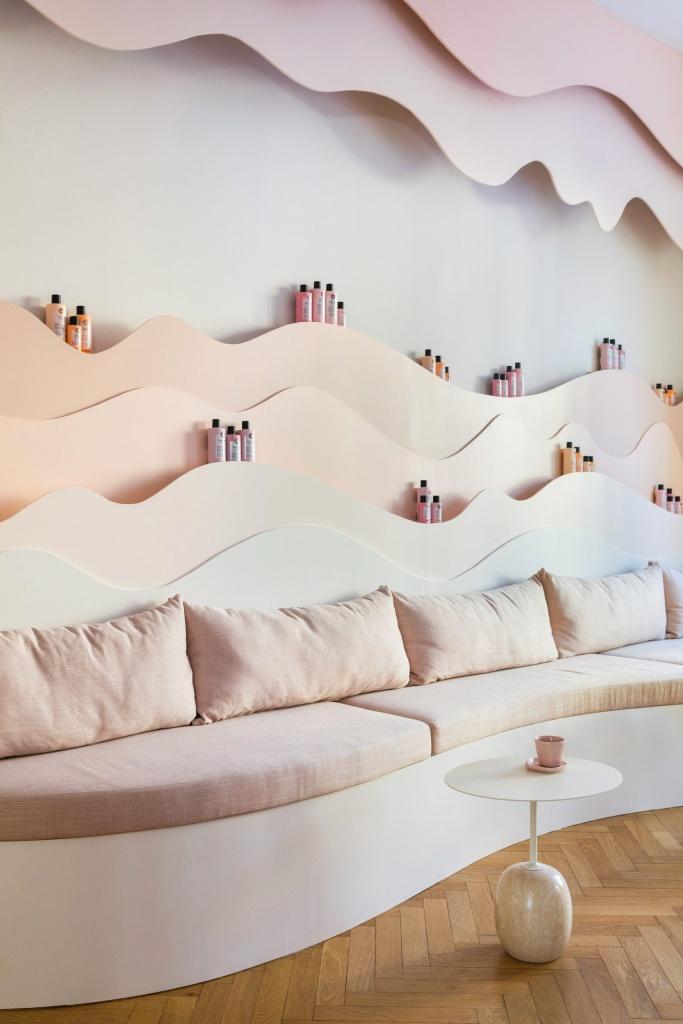 Sofá com almofadas rosa claro. Enfeites na parede e prateleiras em forma ondulada com produtos