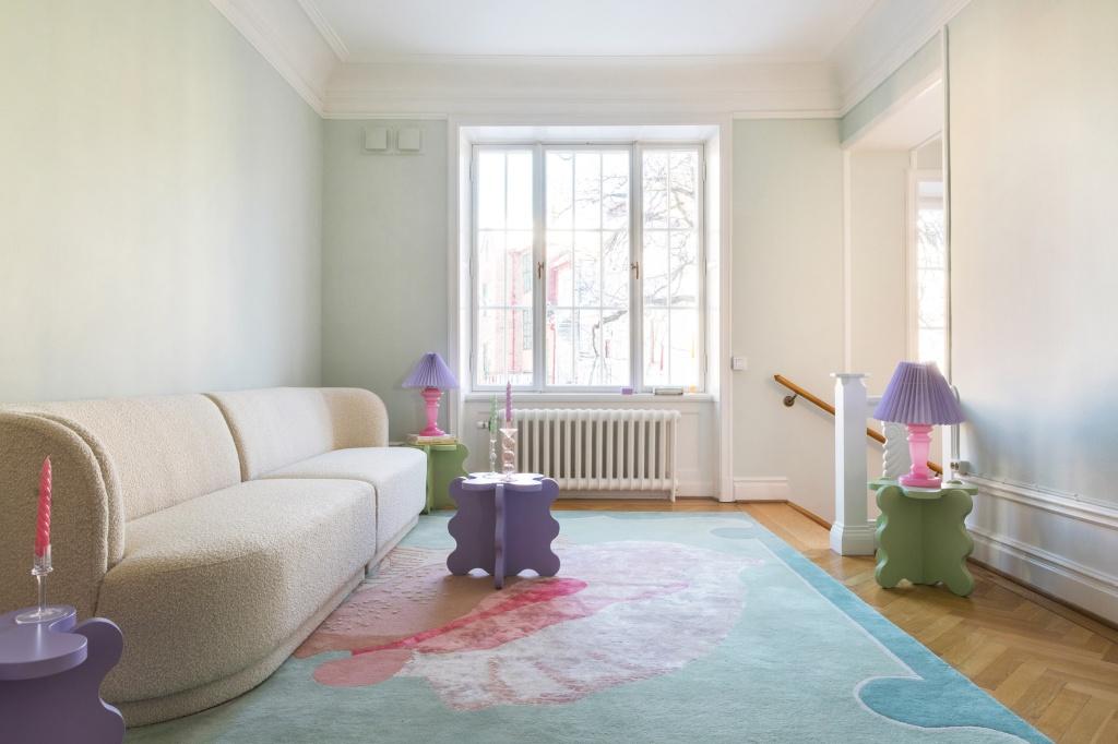 Sala com tapete azul e flor rosa. Sofá off white. Móveis ondulados roxos. Abajures com base pink e topo roxo.