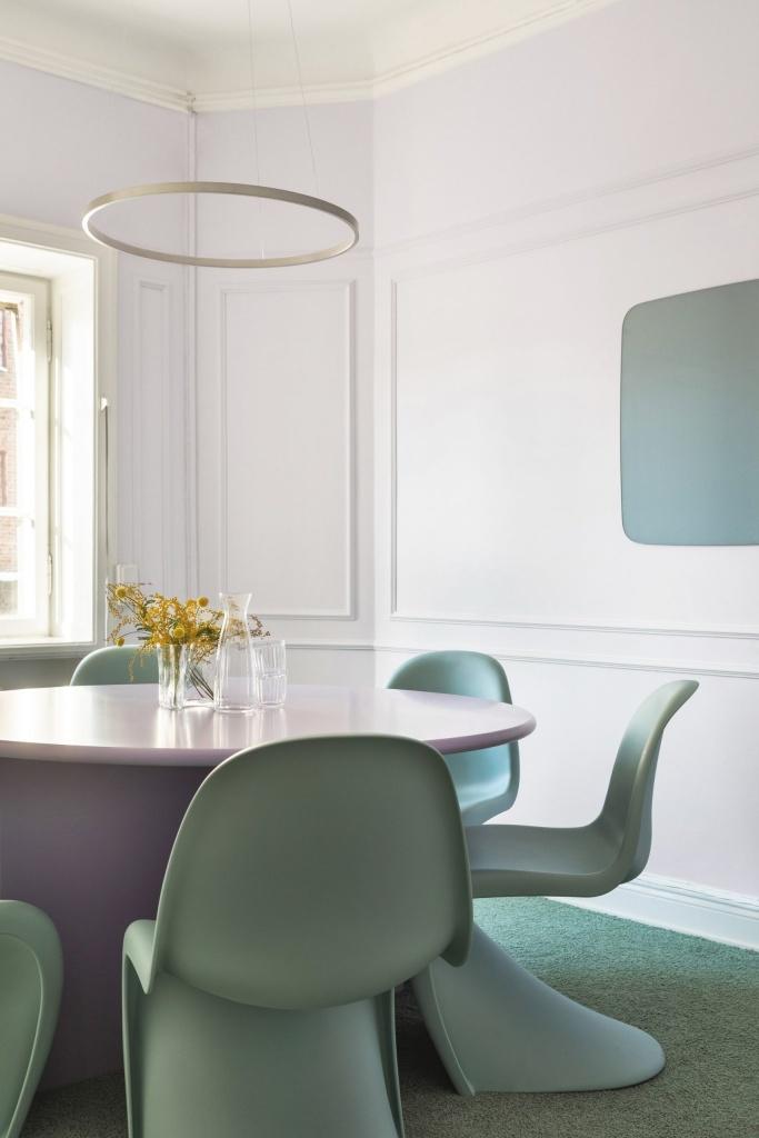 Estar com mesa roxa e cadeiras verdes. Paredes brancas. Luminária em forma de círculo