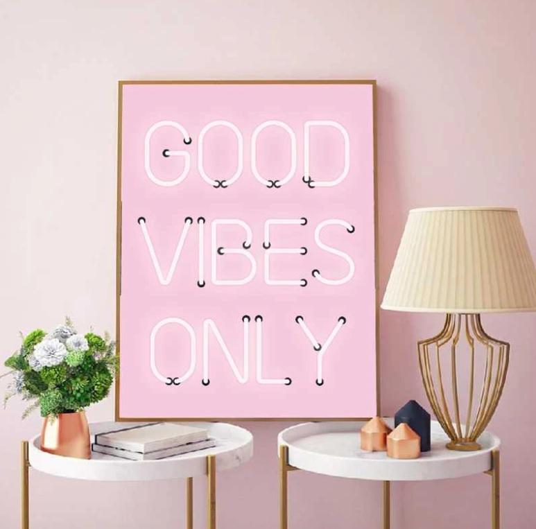 Quadro rosa com letras em neon escrevendo Good vibes only. Duas mesinhas brancas de tampo redondo com abajur e vasinho de flor