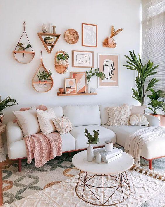 Estar com sofá branco e almofadas brancas e rosa claras. Uma almofada em formato de concha. Na parede, quadros, vasos de plantas e uma prateleira com pequenos quadros
