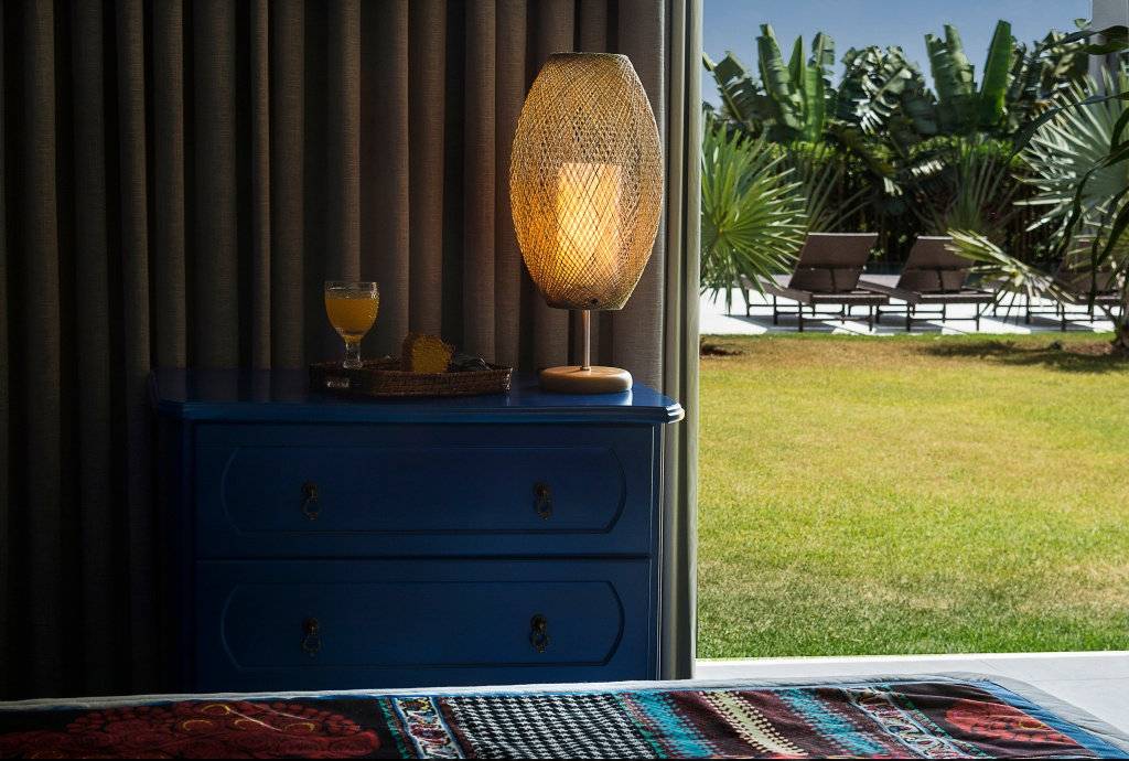 Sala com vista para campo, com abajur com cupula vazada dourada, sobre móvel de madeira azul