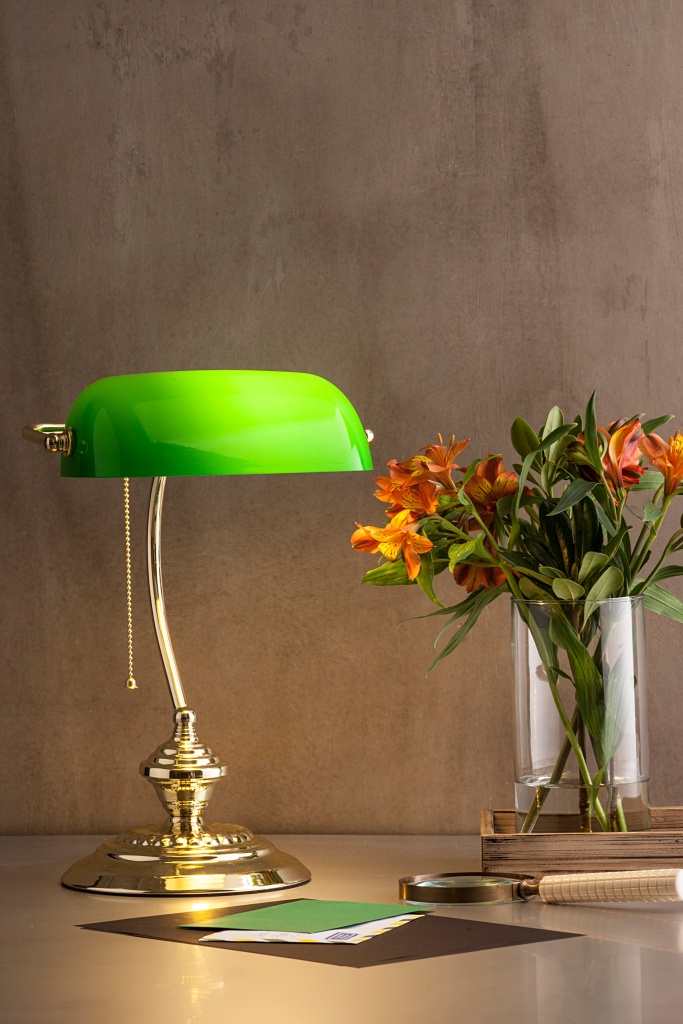 Luminária estilo clássico na cor verde neon, sobre mesa com vaso de flores