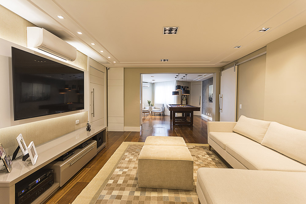 Sala de TV com sofá branco e pufes brancos. Tapete de quadriculados claros.