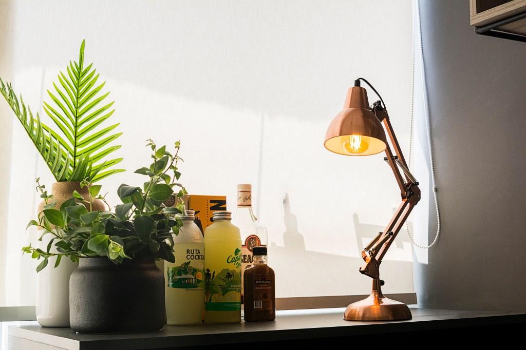 Luminária de mesa flexível na cor cobre sobre mesa com bebidas e plantas