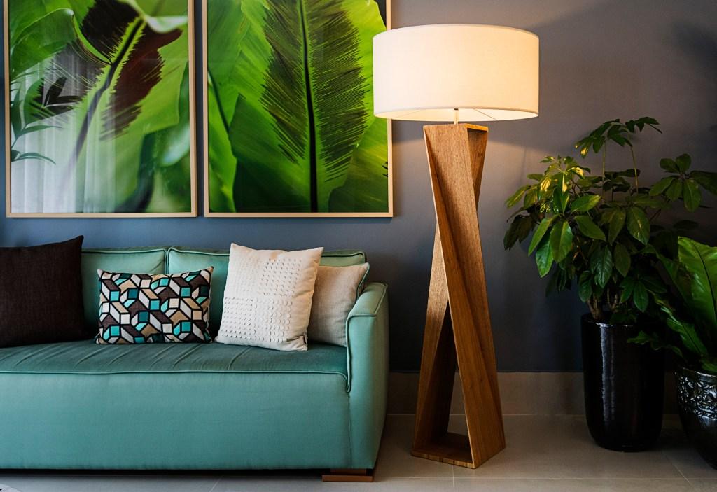 Luminária de piso com suporte de madeira e cúpula branca ao lado de um sofá verde com almofadas brancas e quadro de plantas na parede