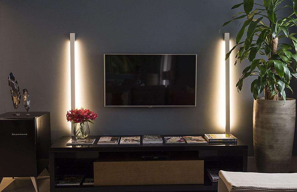 TV iluminada em ambos os lados por luminárias em formato de linha. Hack preto