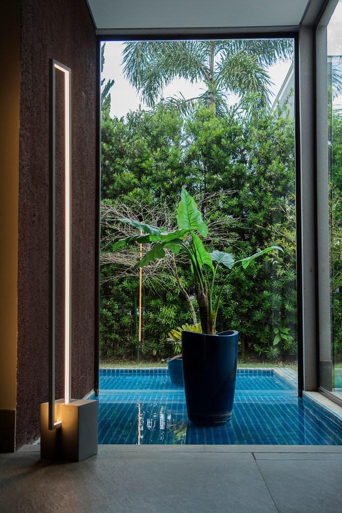 Luminária minimalista ao lado de uma planta grande e uma parede de vidro com vista para o quintal