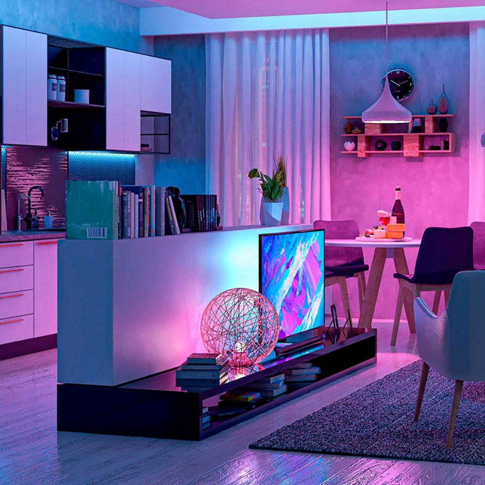 Hack preto baixo com tv. Luminária branca pendente do teto iluminando com luz de cor rosada.