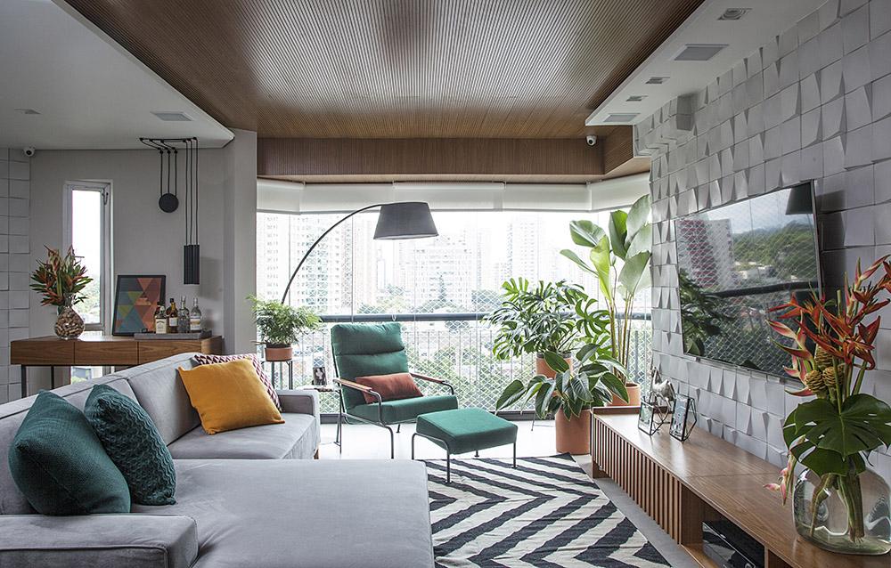 Sala de Tv com tapete preto e branco. Sofá cinza com almofadas verdes. Luminária de piso sobre poltrona verde. TV sobre hack de madeira e parede com revestimento cinza 3D