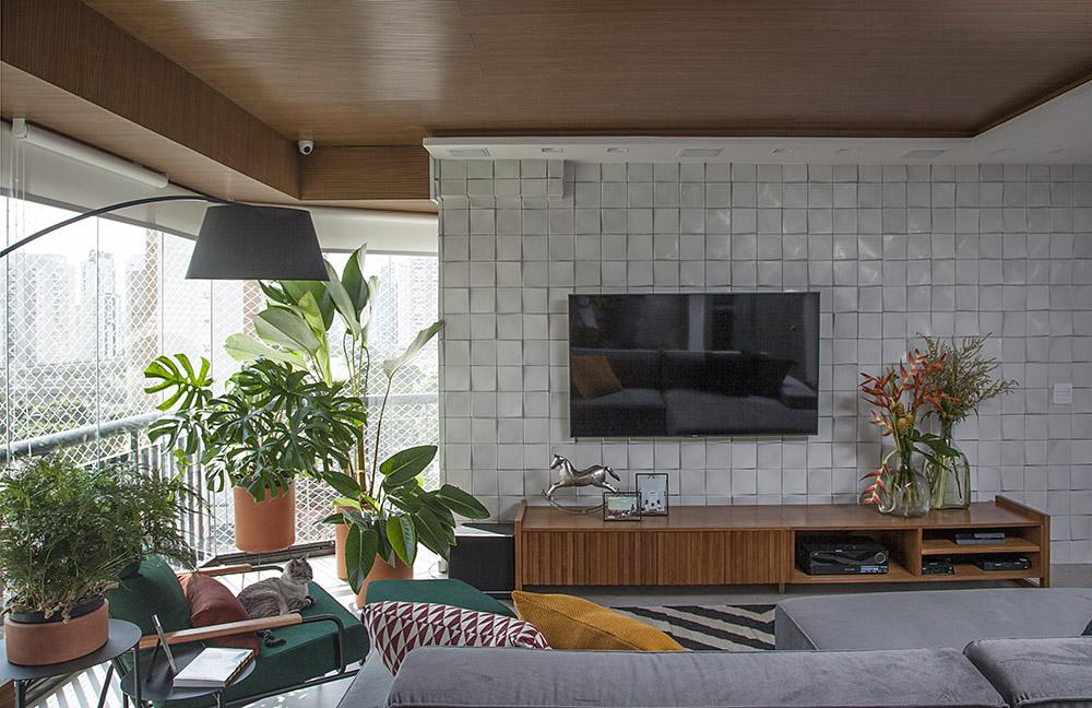 Sala de TV com revestimento cinza 3d. Luminária de chão sobre poltrona verde. Plantas no canto do cômodo