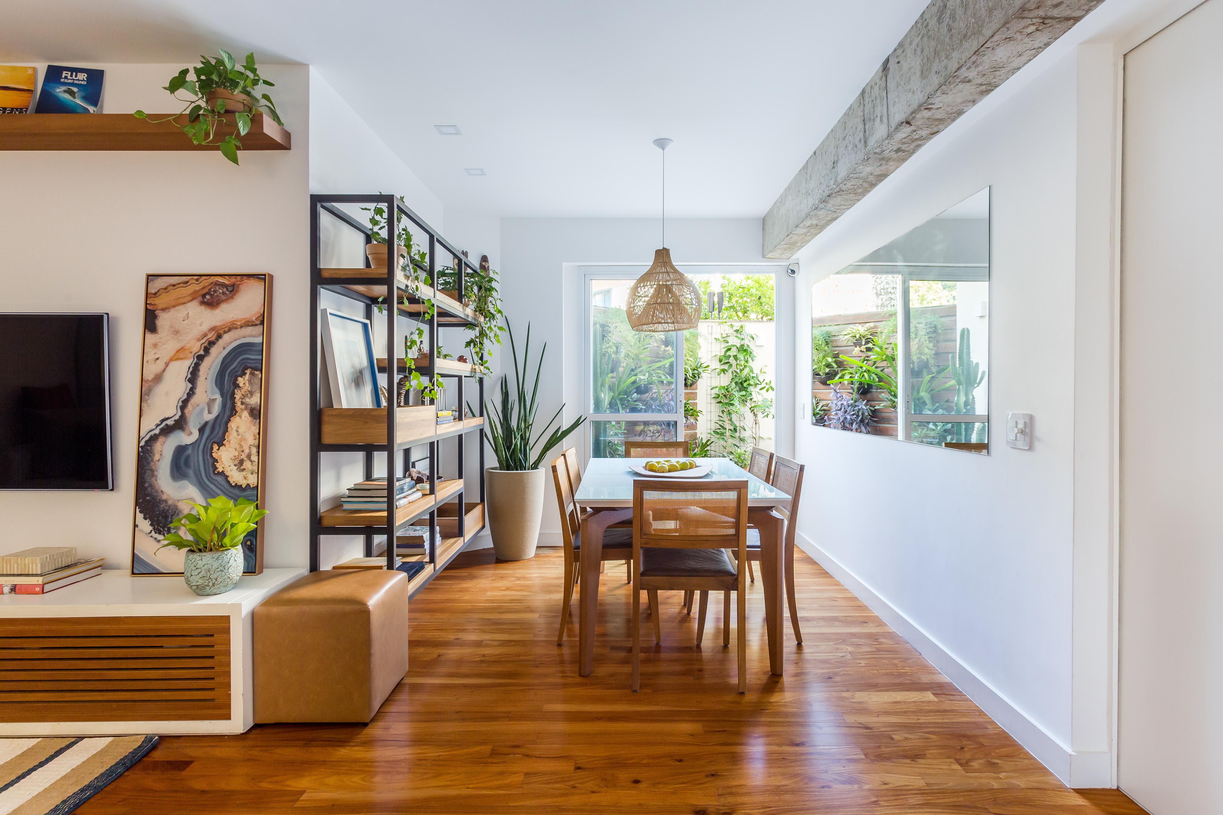 Sala de jantar com fundo de varanda e bastante iluminação natural. Estante de estilo industrial, piso de madeira e base de decoração neutra