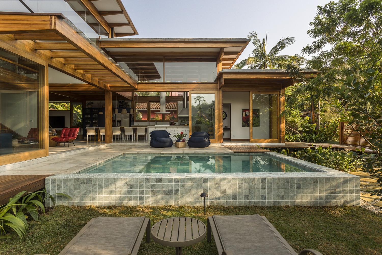 Área externa de casa com piscina e bastante natureza