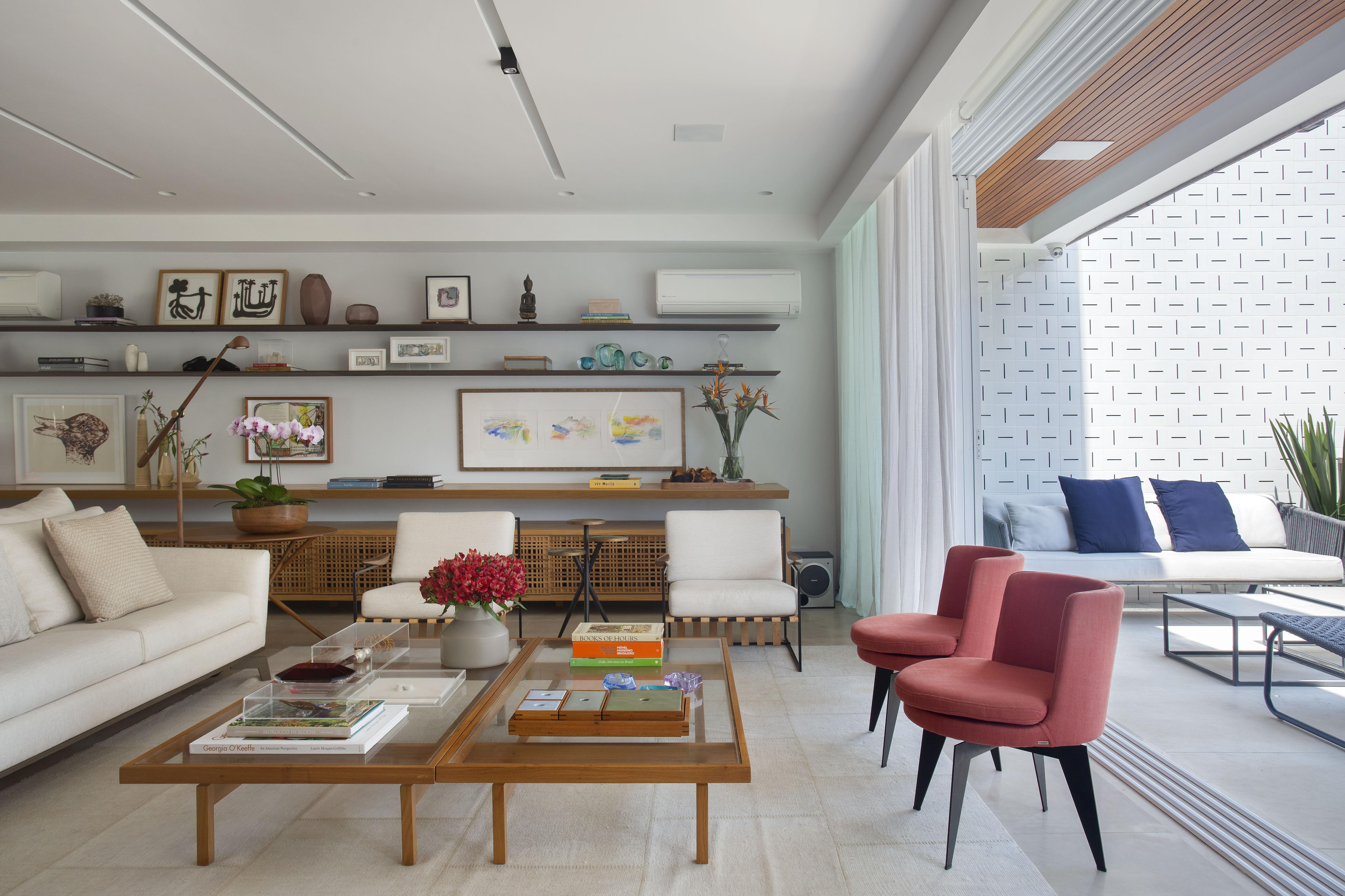 Sala de estar com mesa de centro, duas poltronas vermelhas, sofá branco e varanda integrada