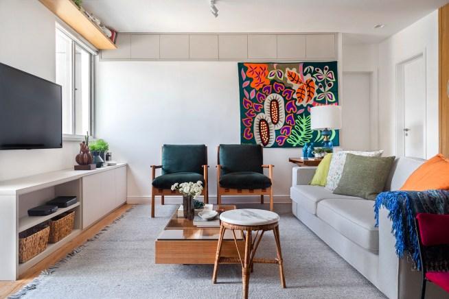 Sala de estar com sofá de cor neutra, duas cadeiras e tapeçaria de parede ao fundo