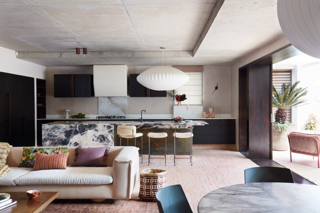 Sala de estar integrada com cozinha, em tons claros, que se conecta ao jardim