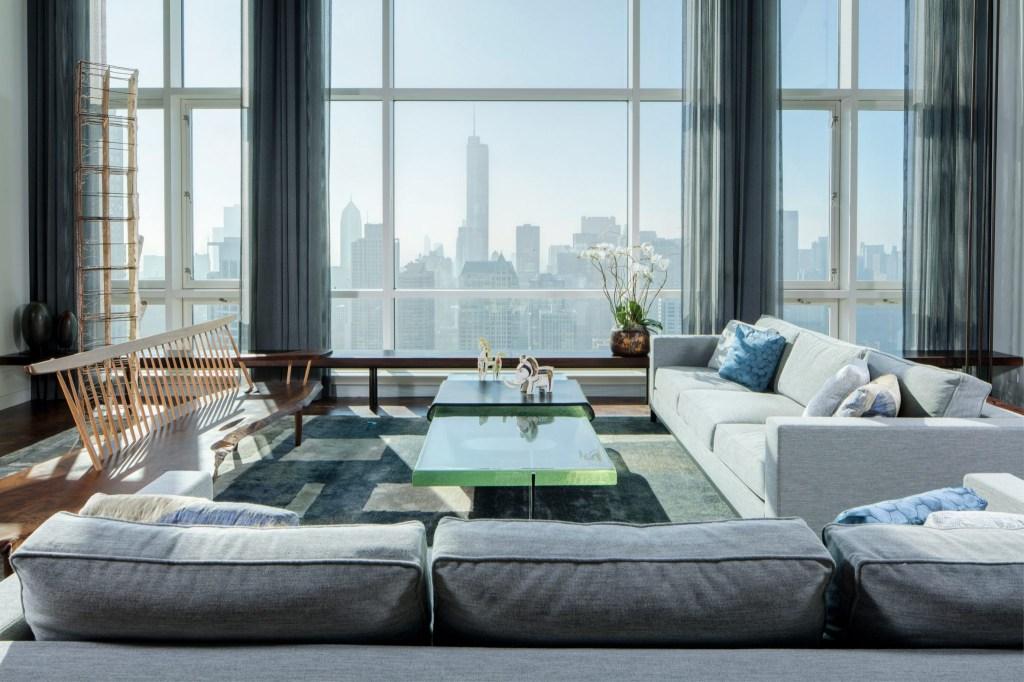 Em frente às janelas do chão ao teto, um grupo de sofás em cores claras é combinado com um tapete combinando em tons calmos de cinza e branco, enquanto uma mesa de centro de vidro seagreen capta a luz das janelas.