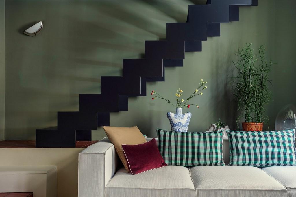 Sala de estar com parede cor verde-musgo Uma escada próxima foi pintada de preto como contraste, criando uma atmosfera temperamental contrastada com as almofadas coloridas do grande sofá