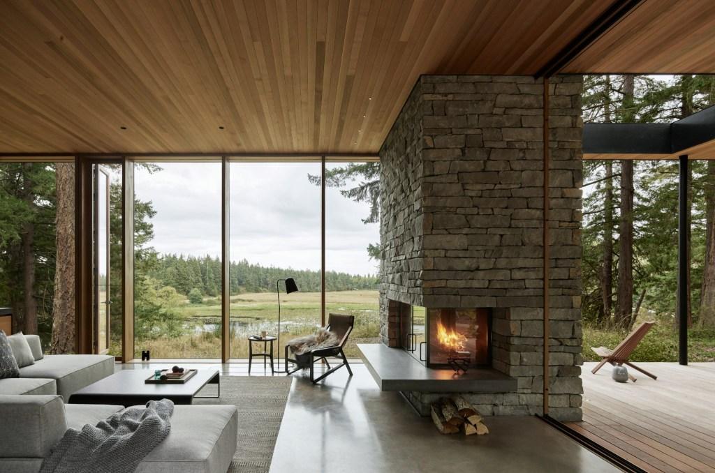 Ambiente calmo com madeira e pedra. Grandes janelas do chão ao teto dão vista para um grande campo aberto