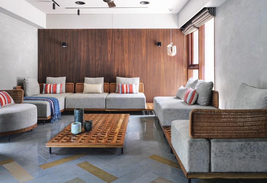 Sala de estar minimalista com sofá cinza, com almofadas coloridas e madeira em uma das paredes
