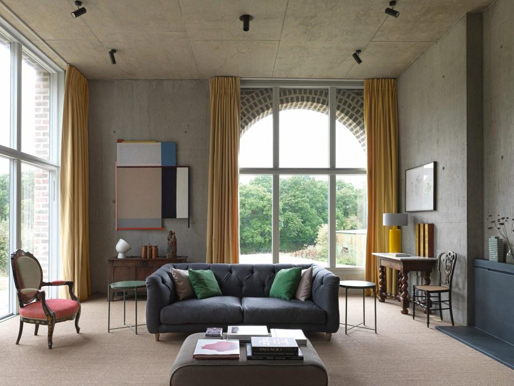 Sala de estar com tetos altos de concreto como um fundo calmo. Uma cadeira de estilo barroco e um banquinho revestido de tecido ajudam a suavizar o espaço.
