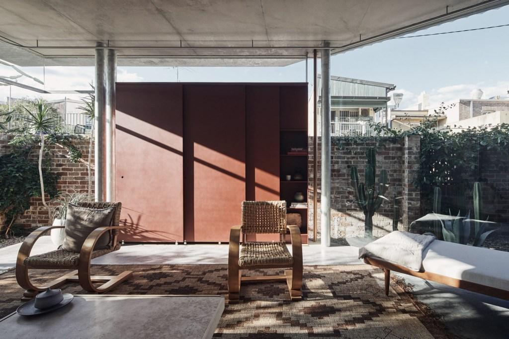Sala com paredes de vidro, com colunas de metal. A mobília tem o mesmo estilo descontraído, com cadeiras de madeira e um sofá-cama, criando locais de descanso confortáveis.