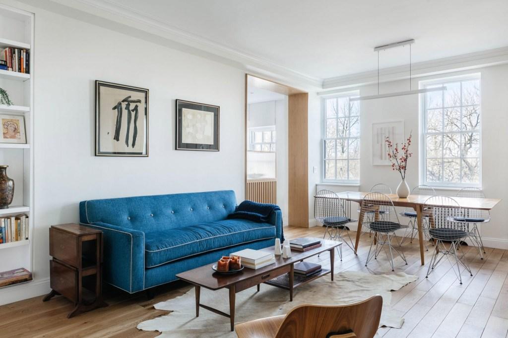 Sala de estar calma com cores claras, piso de madeira e sofá azul