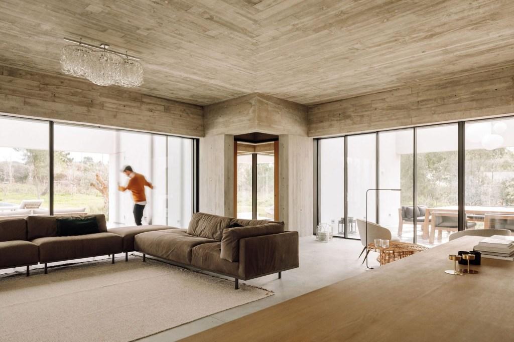 Sala de estar em cores terrosas, com paineis de vidro e revestimento do chão ao teto em cimento queimado