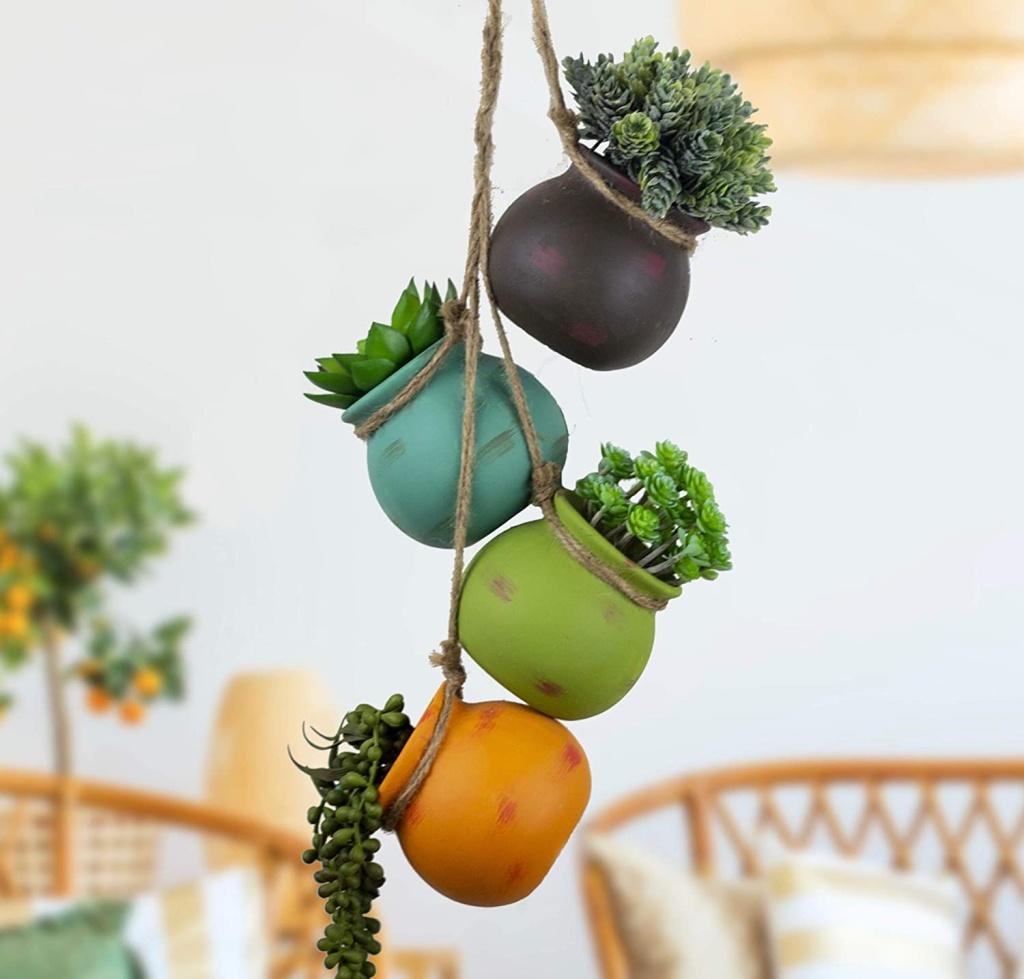 Quatro vasos redondos coloridos com suculenta pendurados em barbante