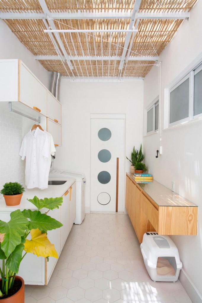 Área de serviço de décor de tons neutros com porta que possui quatro escotilhas