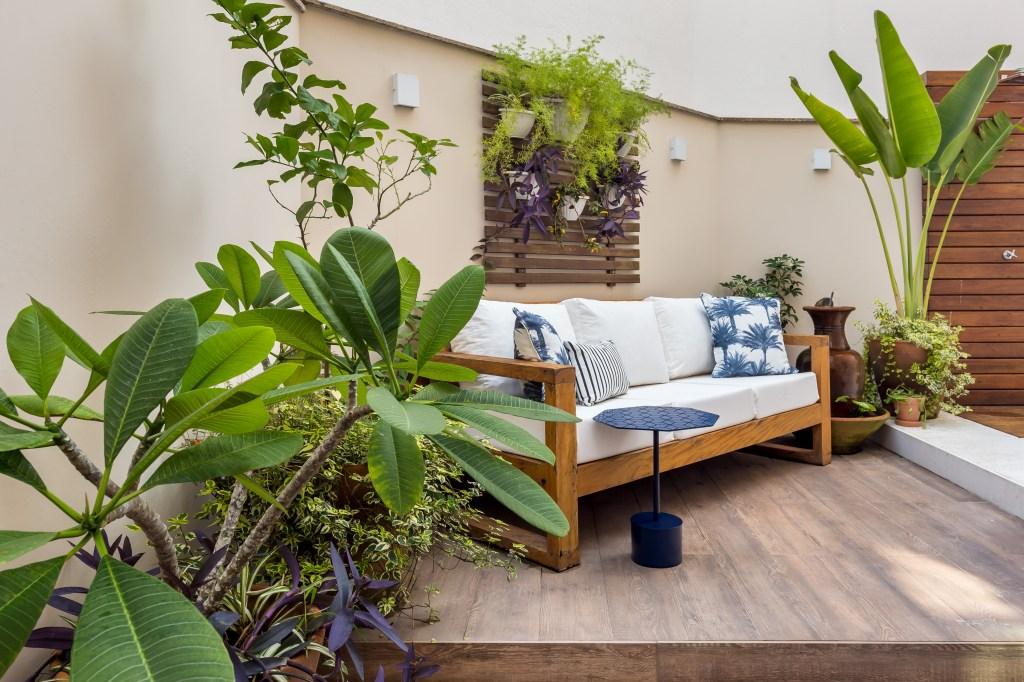 Área externa de um apartamento térreo com paisagismo que lembra quintal de casa, namoradeira branca com marrom e jardim vertical