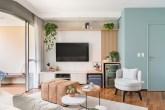 Sala de estar com piso de madeira, marcenaria azul, banco branco, televisão fixa na parede e plantas trepadeiras