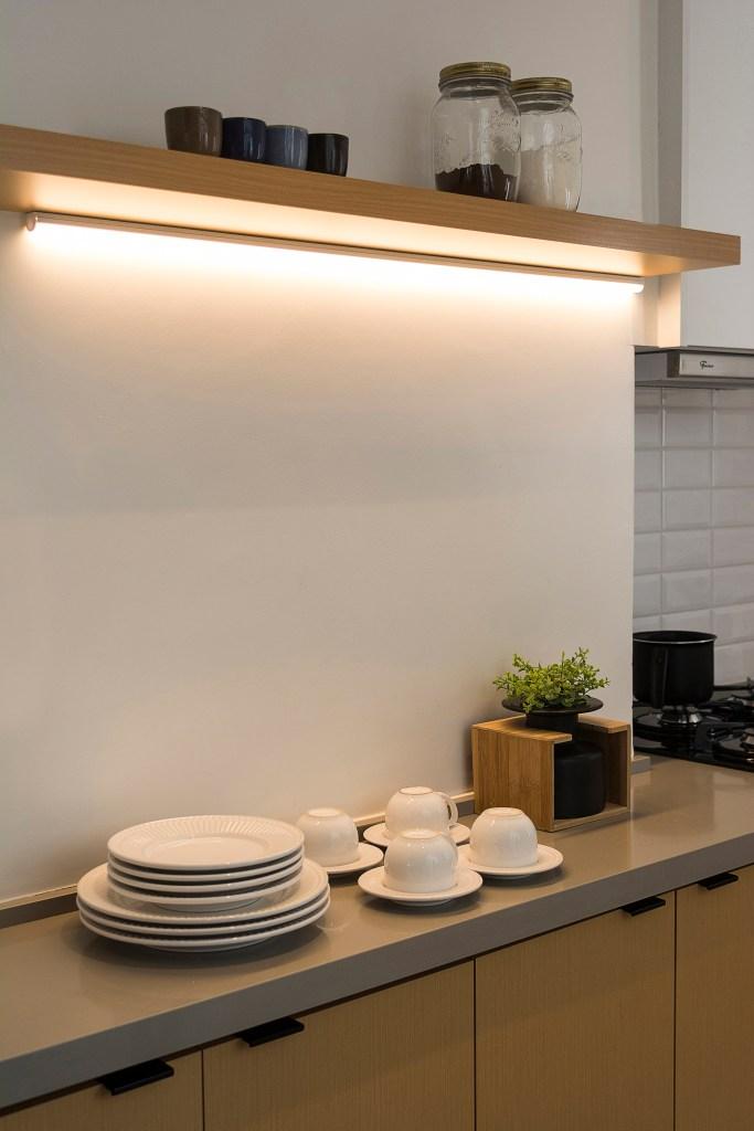 Cozinha com led integrado na estante acima do buffet com tampo cinza e portas de madeira clara