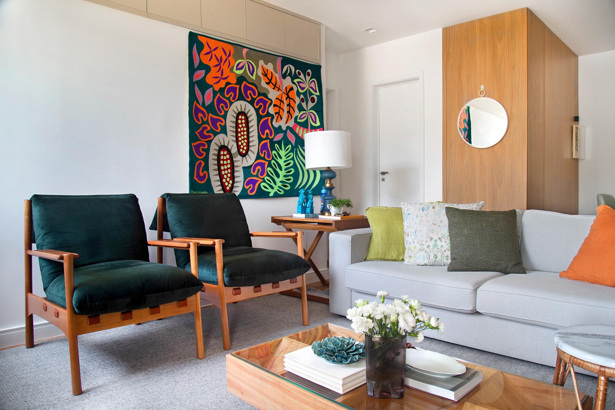 Sala de estar com tapeçaria colorida na parede, duas poltronas verdes, um sofá cinza claro e uma mesa de centro de madeira