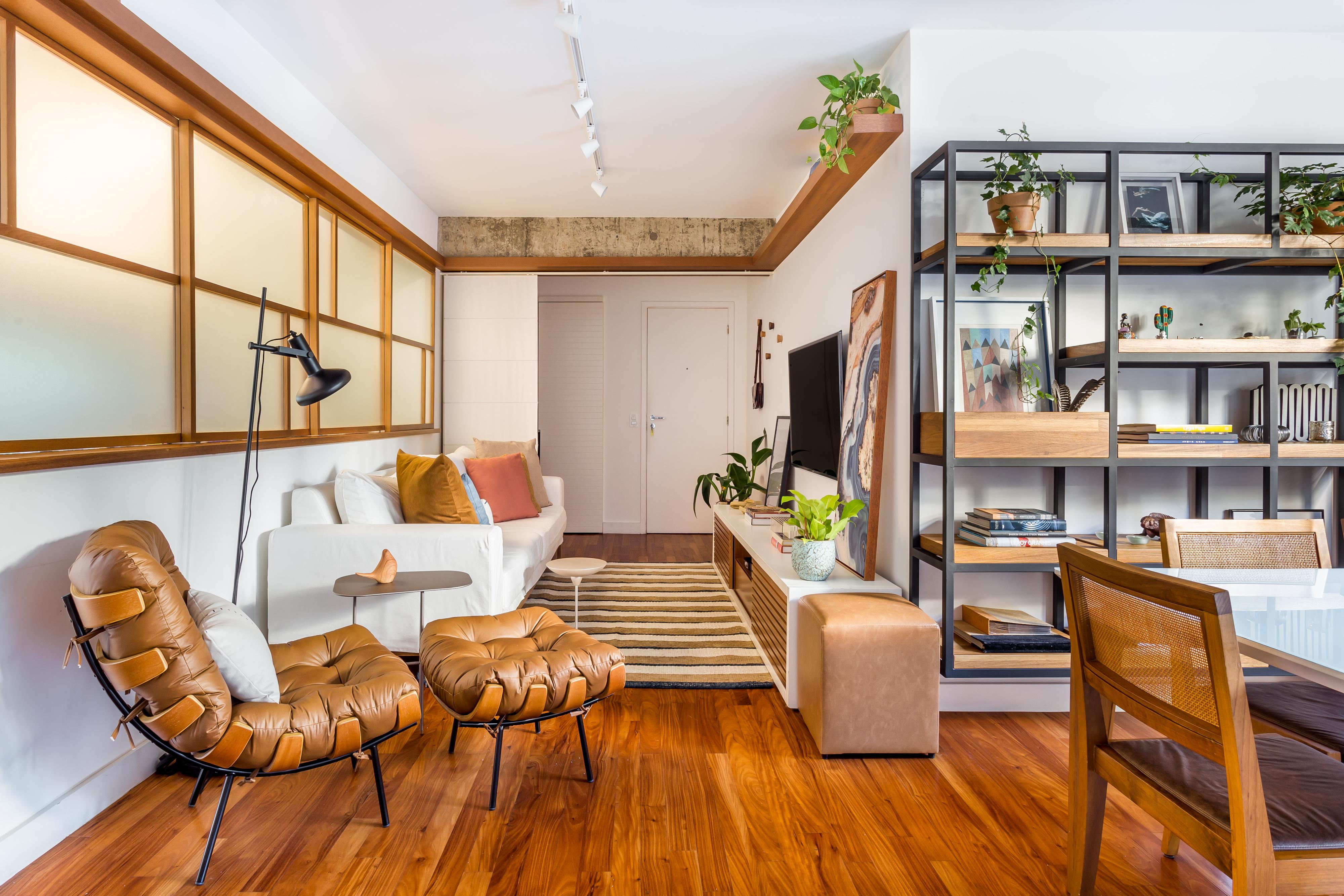 Sala de estar com piso de madeira e décor neutro, estante no estilo industrial, sofá branco e poltrona marrom