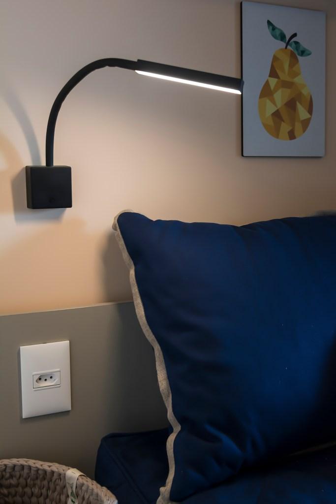 Cantinho de leitura, com arandela preta acima de uma almofada azul, em parede metade branca e metade cinza