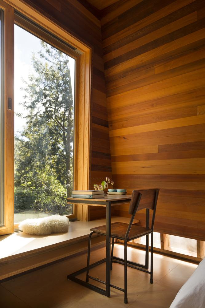 Quarto e home office do pavilhão com vista para a natureza circudante e cadeira, tudo revestido por madeira