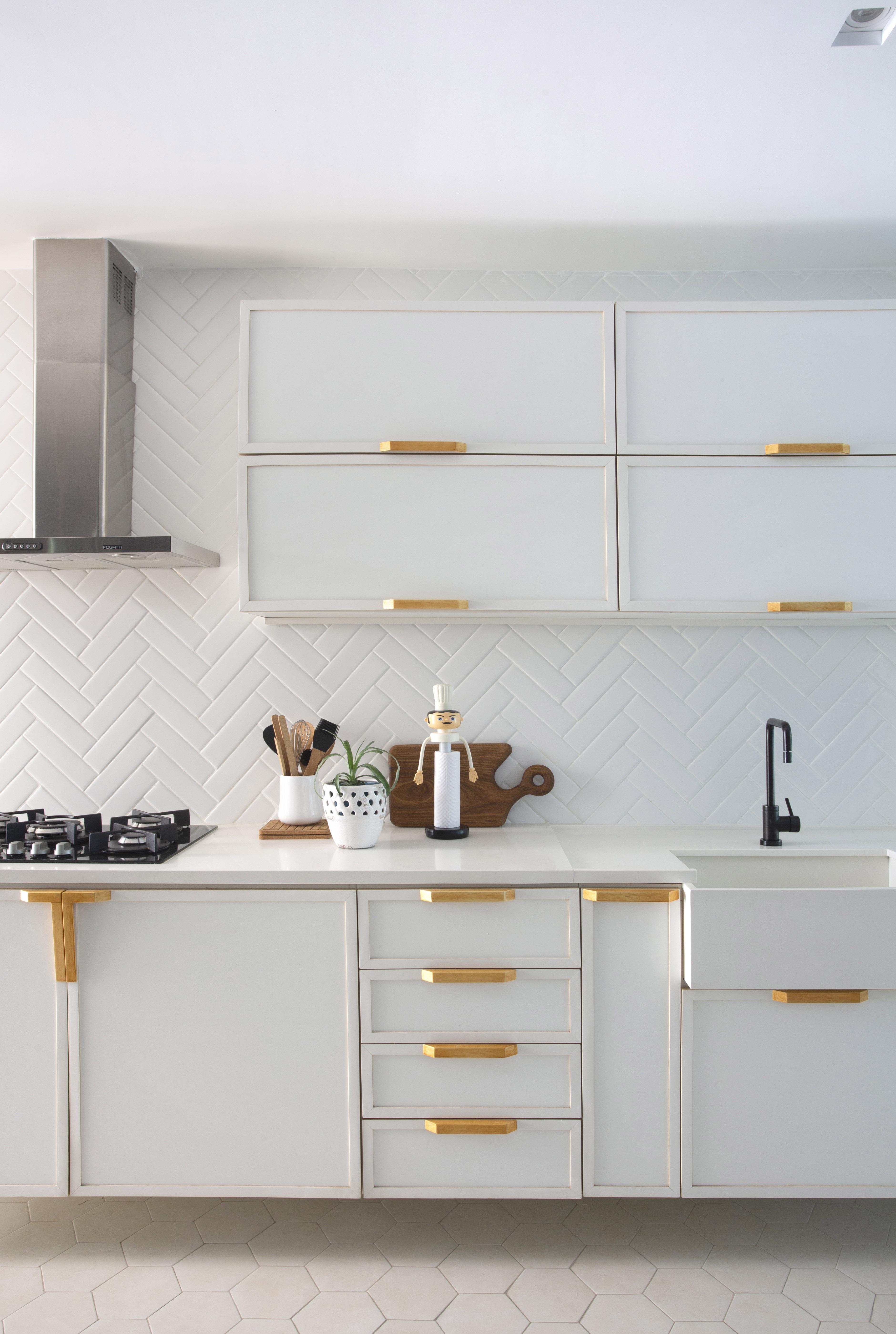 Cozinha com marcenaria clara e puxadores dourados